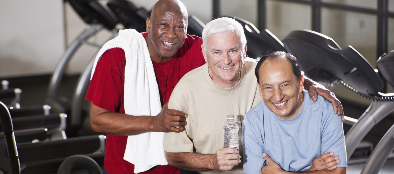 Multi-ethnic senior men (60s) at health club, standing in front of treadmills.